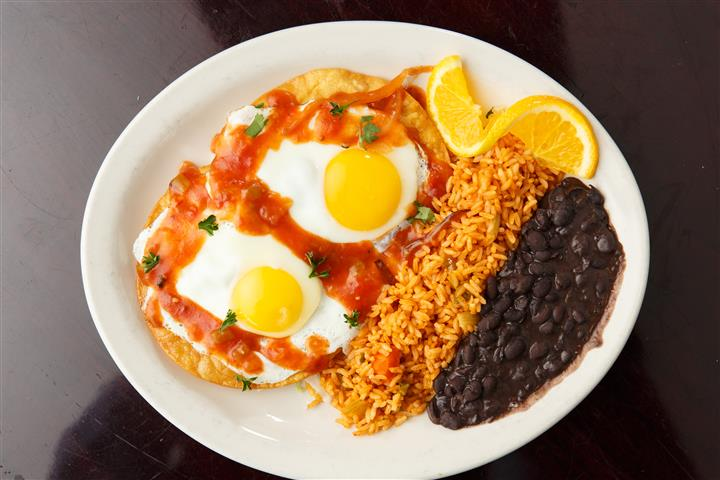 Eggs sunnyside up, rice, and black beans on a platter with a orange slice garnish