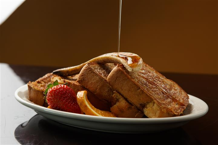 French toast on a platter with strawberries and a lemon slices garnish
