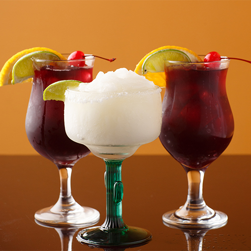 three alcoholic drinks with lemon wedges and cherries