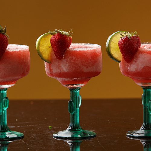 three strawberry margaritas with a lemon wedge and strawberry on side of the glass