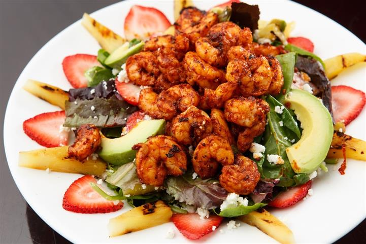Salad consisting of avacados, strawberries, and shrimp