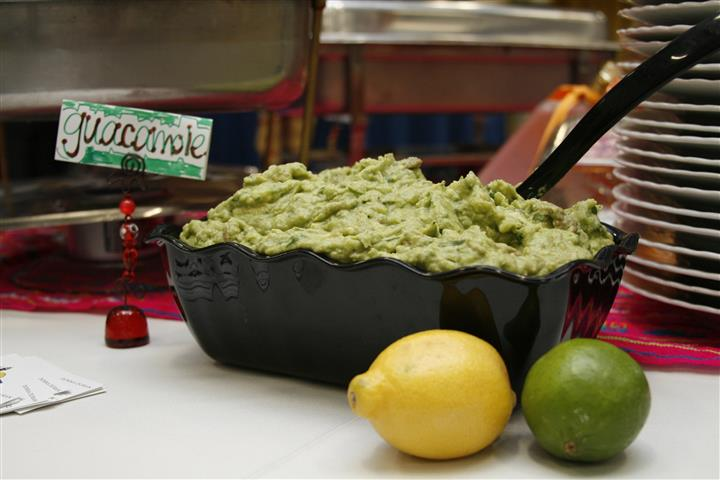Guacamole in a dish with a lemon and lime to the side