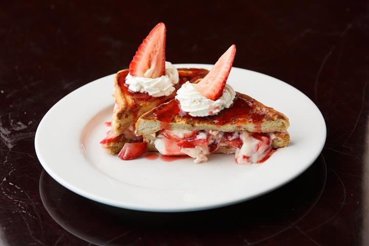 French toast topped with cream and strawberry slices