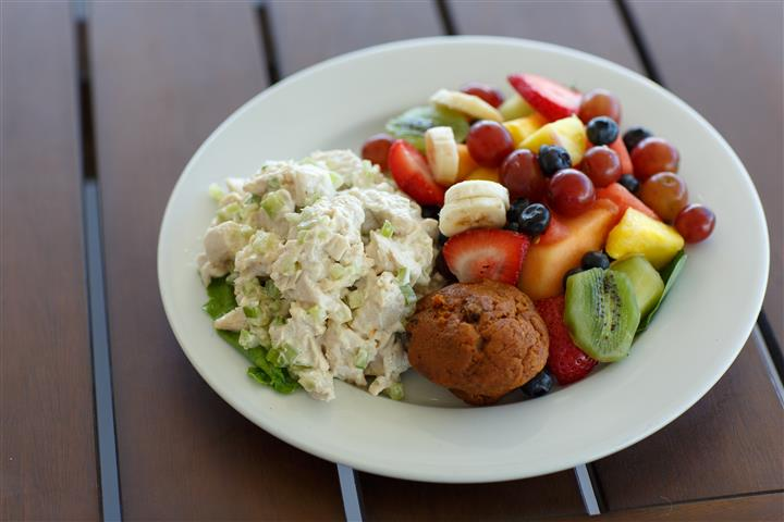 Potato salad and muffin with fruit salad on a plate