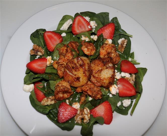 Salad consisting of strawberries, shrimp and feta cheese crumbles