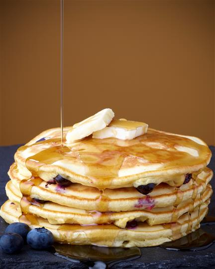 Blueberry pancakes with syrup and butter
