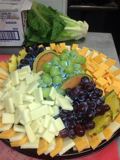 A cheese platter served with grapes and pineapple clies
