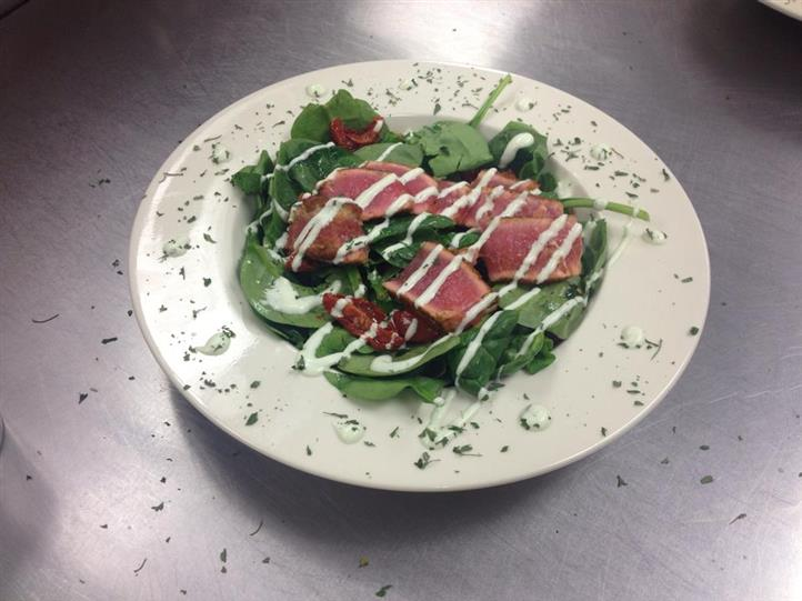 Spinach salad with bacon and sun-dried tomatoes, topped with dressing