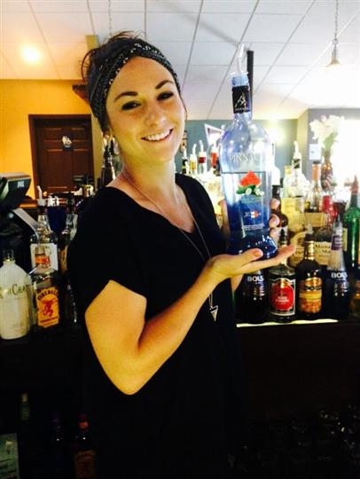 A young bar woman smiling posing for a photo at the behind the bar holding a blue alcoholic bottle.