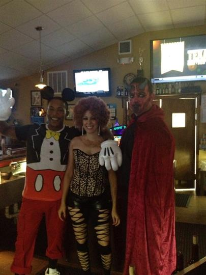 Two men and a woman dressed in Halloween suits, possing for a photo