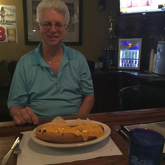 A man smiling for a photo sitting at the bar in frond of a hot dog.