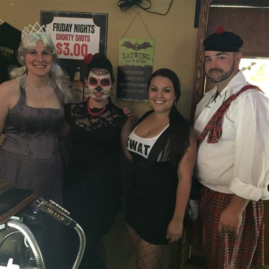 Four people dressed in Halloween dresses posing for a photo