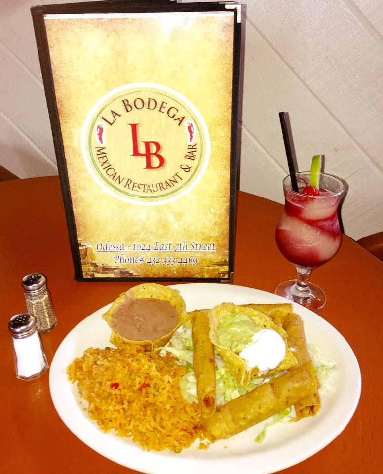 taquitoes with sides of rice, refried beans, sour cream, and guacamole, served with a mixed drink