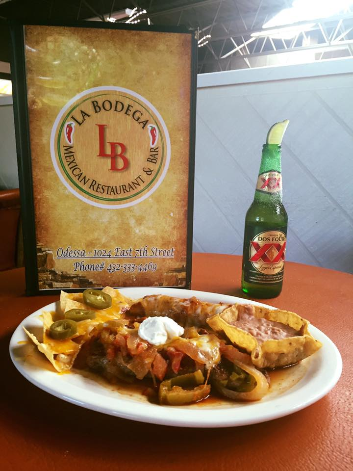 enchiladas and nachos topped with cheese, jalapenos and sour cream, served with a Dos Equis beer with a lime wedge