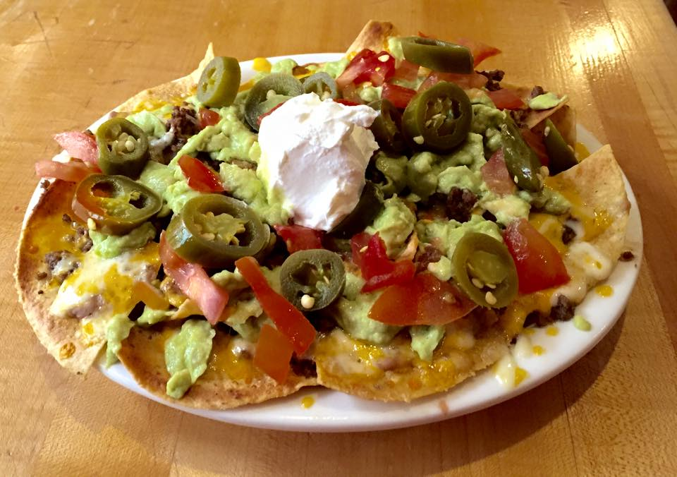 nachos with cheese, guacamole, sour cream, tomatoes and jalapenos