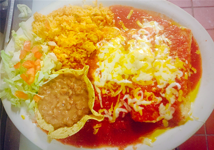 enchiladas covered in cheese and sauce, with a side of rice, refried beans and lettuce