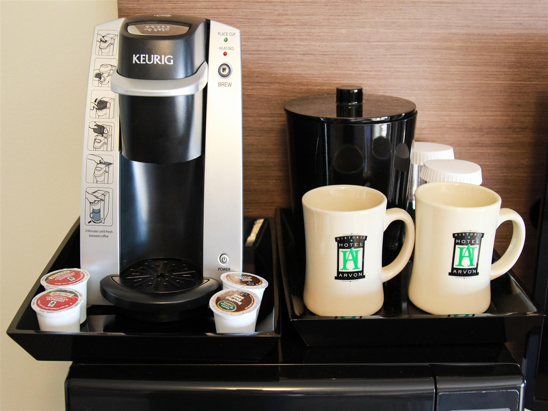 keurig being displayed with two mugs and coffee pods