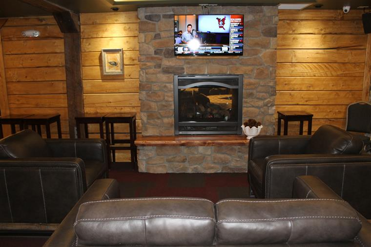 couches facing  fireplace and TV above