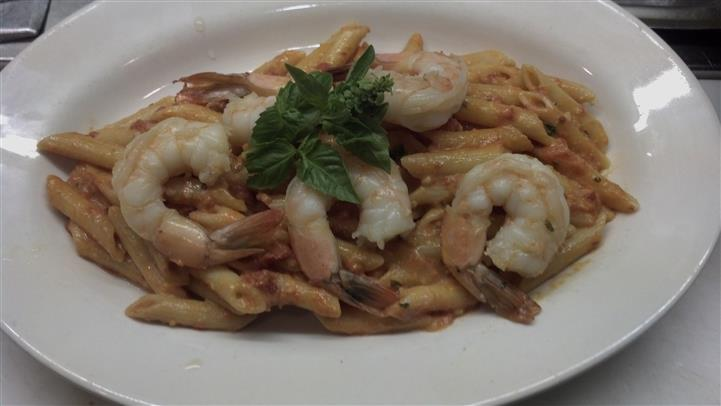 Penne pasta in a light cream sauce with shrimp.