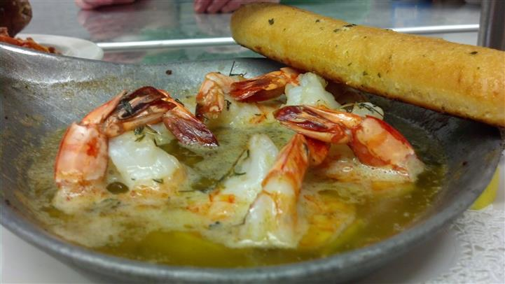 Shrimp in a dish of butter with a garlic bread stick.