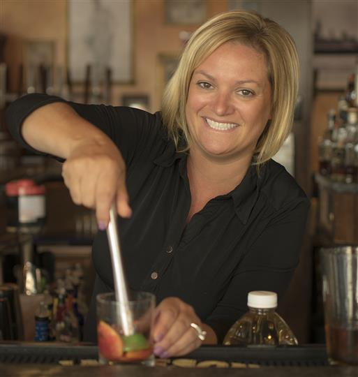 waitress preparing a mixed drink at the bar smiling for the camera