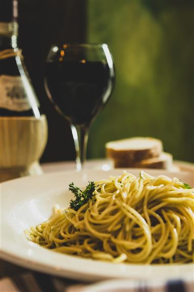 spaghetti noodles with a glass of wine in the background