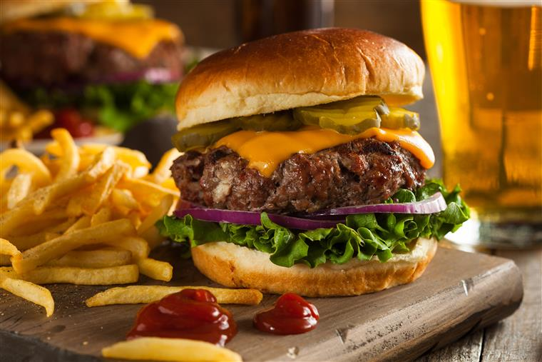 Thick, juicy cheeseburger with lettuce, onion, pickles on bn with side of fries and ketchup on wood carving board, glass of beer and another hamburger in background.