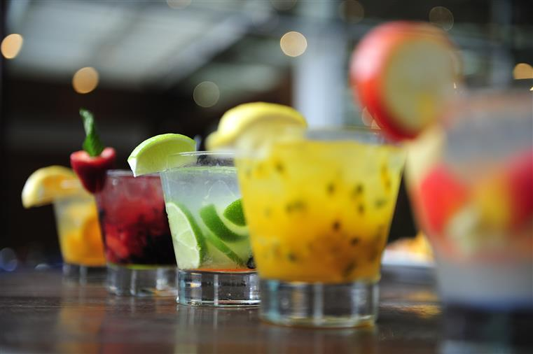 Row of mixed fruity cocktails on bartop.