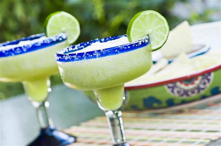 Margaritas with salted rims and lime slices on festive tablecloth.