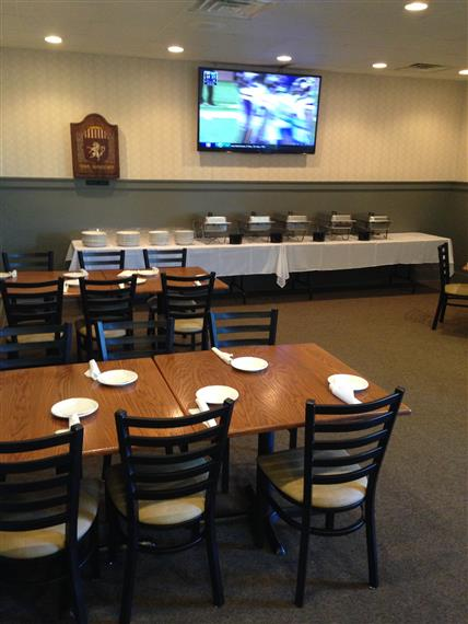 Interior of catering room showing buffet-style table and dining tables. Television on rear wall.