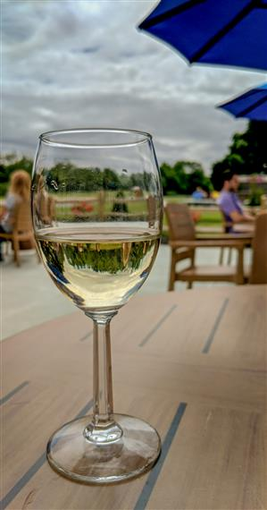 Half-filled glass of white wine in foreground on table, patrons at outdoor seating in background.