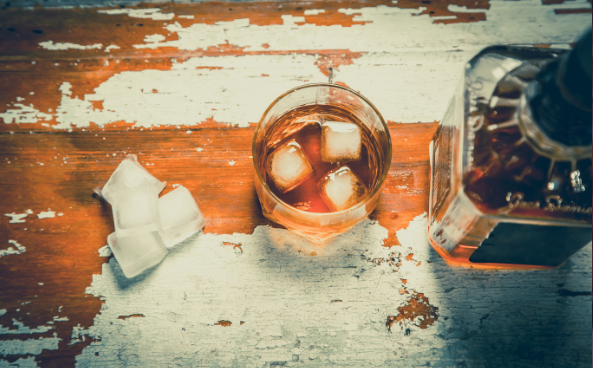 Whiskey bottle and glass of whiskey with ice on faded wooden table top view