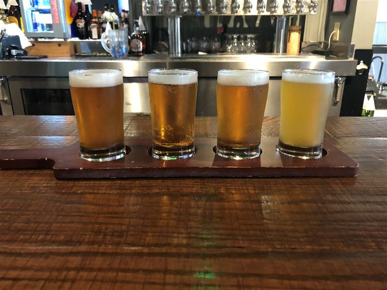 I P A beer flight on bar counter.