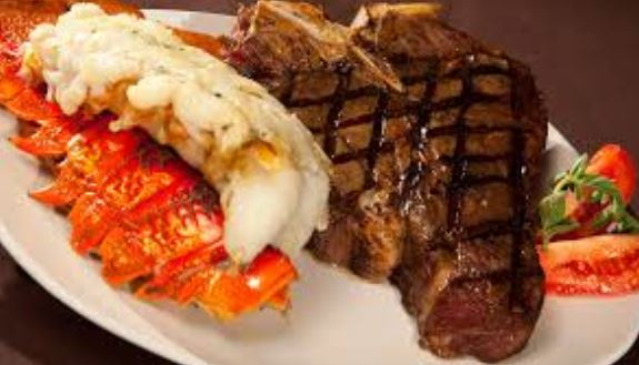 Grilled New York strip steak with lobster tail on white dish.