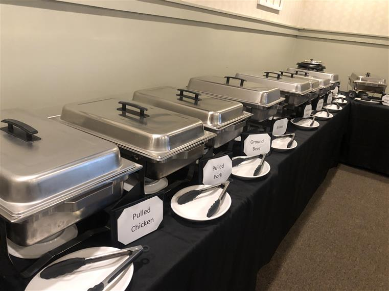 Various hot dishes displayed in hot pans lined up on table