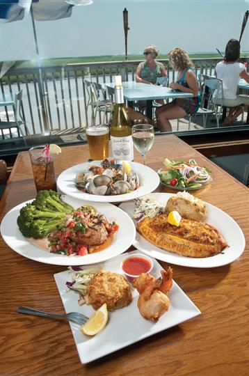 Variety of seafood dishes and vegetables with beer, wine, iced tea on table overlooking marina