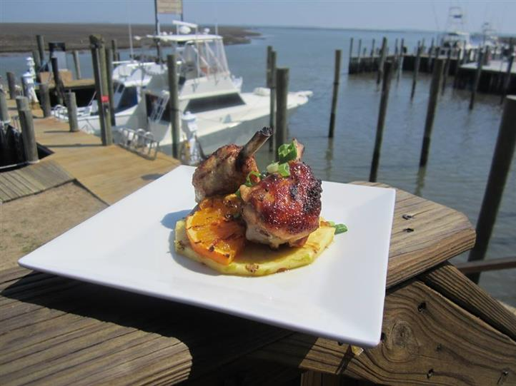 Pork chop over orange wedge and pineapple slice, topped with scallions on dish on ledge of dock overlooking boats in marina