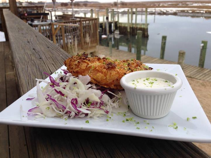 Fried fish over shredded cabbage with dipping sauce on dish on ledge of dock overlooking boats in marina