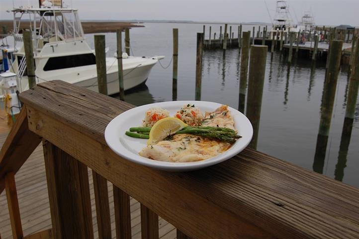 Fish with rice and asparagus on dish on ledge of dock overlooking boats in marina