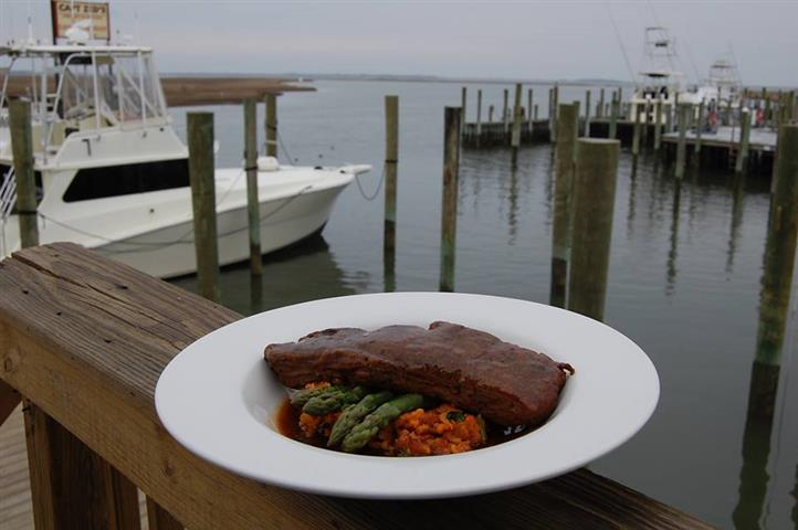Steak over asparagus in dish on ledge of dock overlooking boats in marina