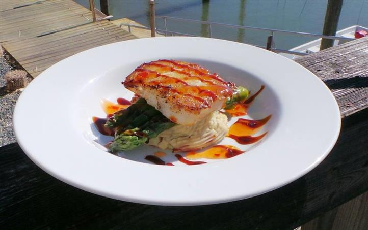 Fish over asparagus and mashed potatoes on dish overlooking marina