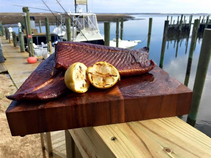 Smoked salmon filets on wood block on ledge of dock overlooking boats in marina