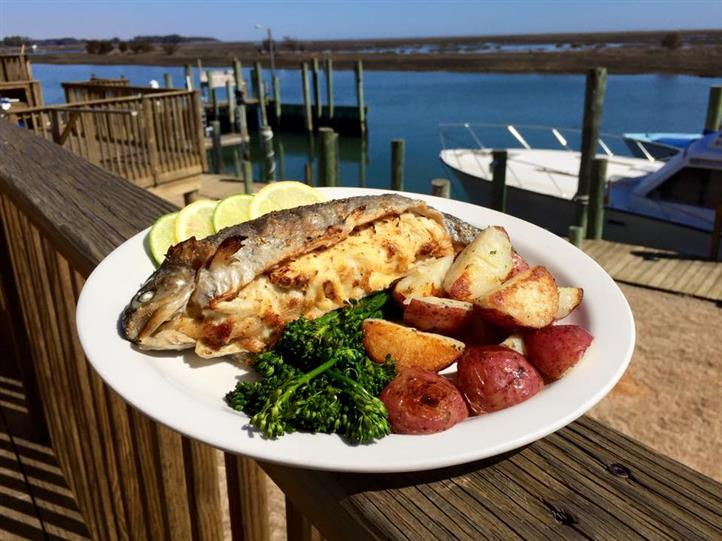 Stuffed flounder with red potatoes and vegetables on ledge of dock overlooking marina.