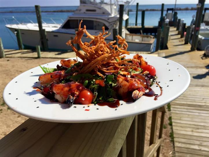 Shrimp salad with onion straws on ledge of dock overlooking boats and marina