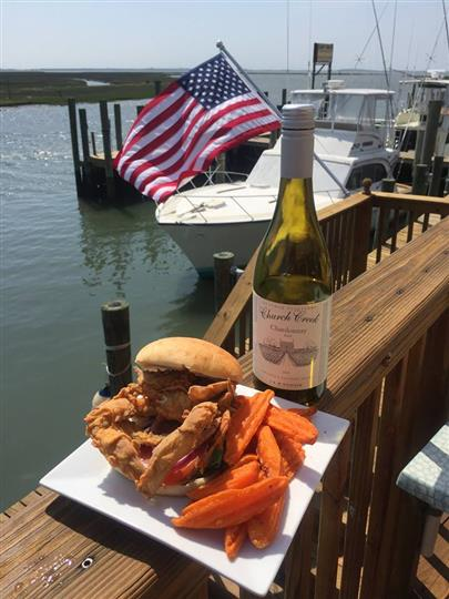 Soft shell crab sandwich with side of sweet potato wedges and bottle of wine on ledge of dock overlooking boats in marina.