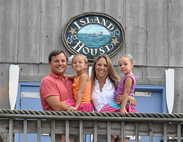 Family posing for photo in front of Island House sign on wood building