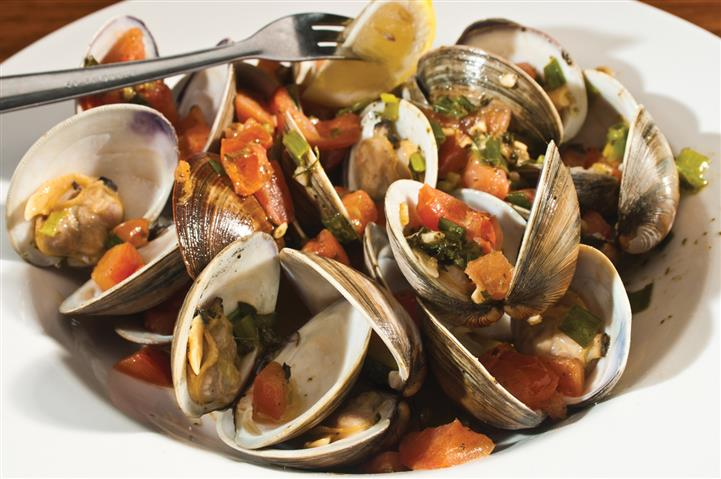 Lemon on end of fork over dish of open clams.