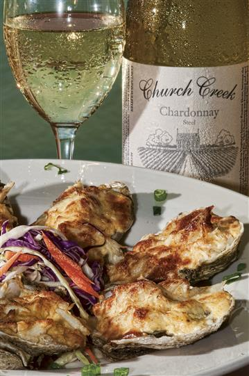 Oysters on half shell in front of chardonnay bottle and glass of chardonnay