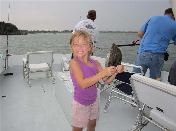 Young girl holding caught fish on boat