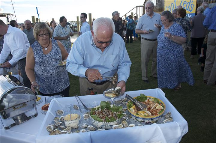 Man helping himself to oysters at buffet station